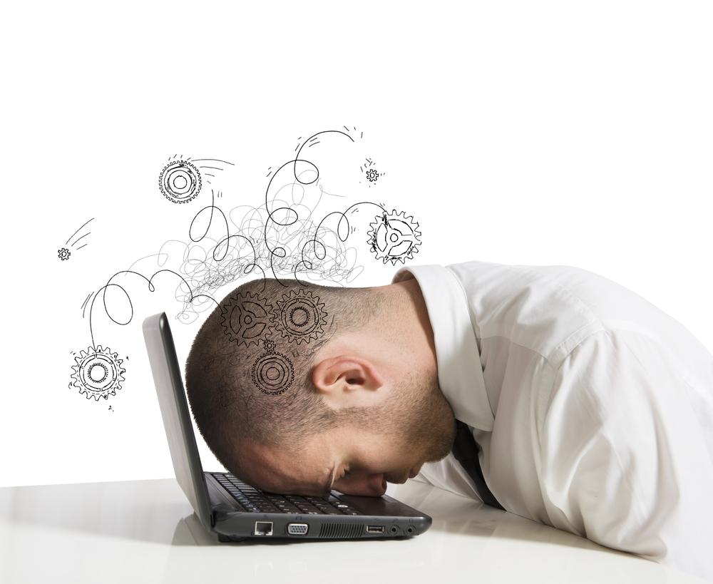 Employé posant sa tête pleine de pensées sur son pc portable