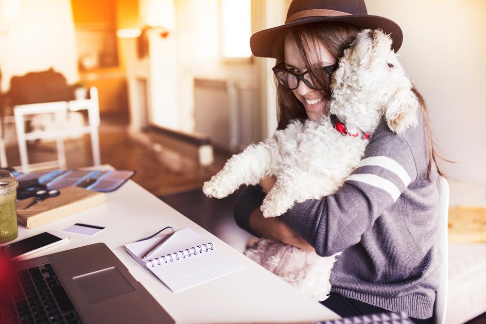 employée heureuse faisant un calin à un chien devant son bureau